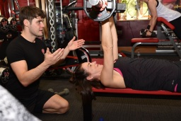 Female doing a chest press with a personal trainer