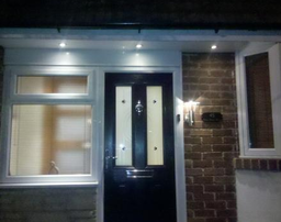 Low voltage spotlights illuminating a front door and access step. Outside lantern to the side of the front door