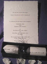 Scroll invitations with embossed design with feather and heart detail on the ribbon band. The colours can be changed to suit your own colour scheme.