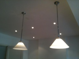 Pendants over an island surrounded by downlights.