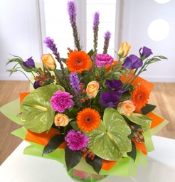 Harlequin Delight   A vase full of colour - lime Anthurium, orange Gerbera and the ever popular Rose are mixed with purple Lisianthus and Liatris.  Vase included.