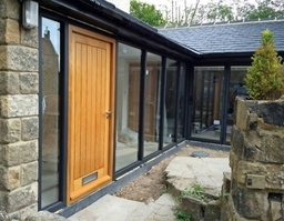 Pushing the design boundaries at Marlin - a handmade oak entrance door incorporated into an aluminium glazing system .