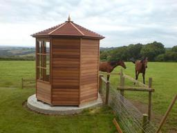 Octagonal summer house installed away from the main house to enjoy the horse's in the field