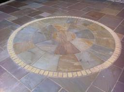Sandstone circle in sandstone patio in Wiltshire garden