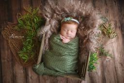 sleepy newborn girl in green