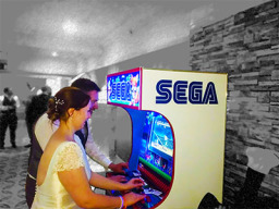 Bride and groom playing arcade games at wedding
