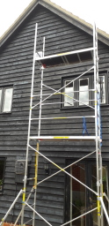 Exterior painting of a barn with scaffold tower