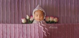 gorgeous sleepy newborn baby girl in pink
