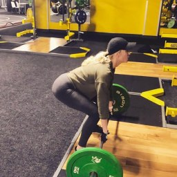 Lady training deadlifts in gym