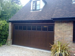 Timber Sectional Garage Door fully finished in dark oak with diamond lead windows