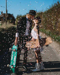 Couple kiss with confetti and skateboards