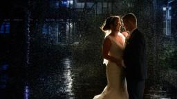 Wedding photo of happy couple in the rain