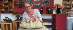 Sarah modelling clay cat lying on its back. In background are examples of Metallic cat figures and plaques