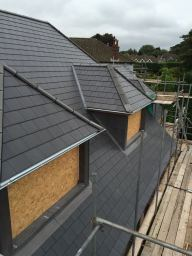 New slate roof with dormers fitted.