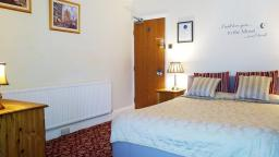 Standard ensuite room 4 overlooks the garden of Chester Brooklands B&B and has tudor building views.
