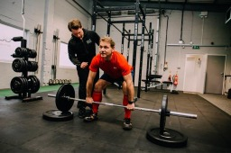 Personal trainer coaching a client how to deadlift