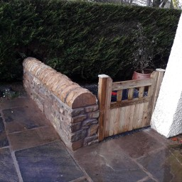 A sandstone garden wall and wooden gate