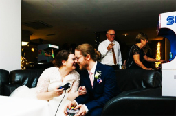 Bride and groom playing video games at wedding