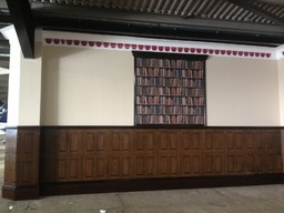 Wallpapered wooden effect panelling and bookcase