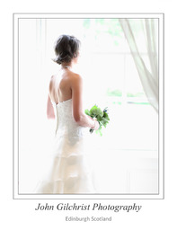 Bride looks out window on her wedding day